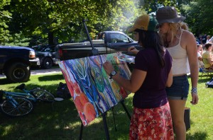 NMU drawing and painting majors Kate Hertler, left, a senior, and junior Kelly Peters, collaborate on a site painting while at Fall Fest on Monday, Aug. 26. Hertler and Peters are part of the new campus organization, HUEnited Artists.
