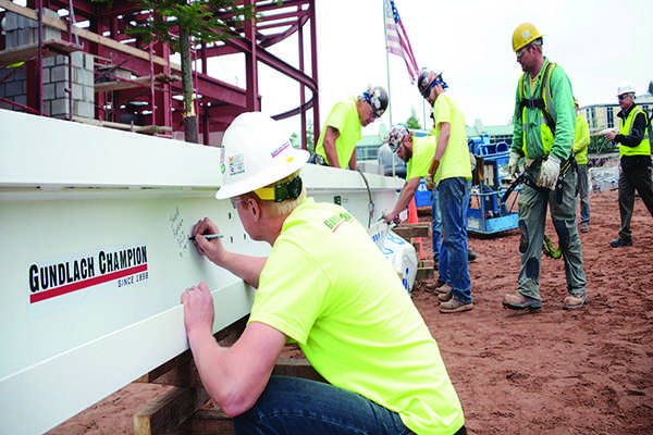 A crew member of the new Jamrich project signs his name on the last beam of the frame. Signing the beam is part of the 'topping-off' tradition, which is a long-time ironworking custom. (Photo: Amanda Monthei)