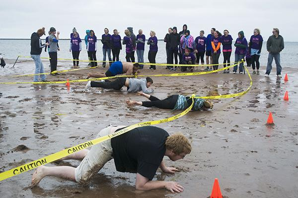 For one segment of the obstacle course, competing students had to get down on all fours to crawl under tape in the wet sand on Superior's shore. (Photo: Katie Stumman)