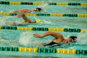 NMU freshman Rachel Borchardt leads, with junior Tara Dowling in the center lane and junior Jordan Iverson in the far lane for the pre-season Green and Gold intrasquad match. (Kelly McCommons