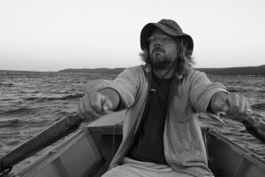 """Johnson summers in Marquette like a """"12-year-old boy,"""" in a row boat drifting and writing. (Photo Amy Howko Courtesy)"""