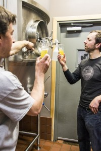 NMU alumni brewmaster Nick VanCourt and Adam Robarge brewery liaison of the Ore Dock, discuss the brew calendar and fermenter locations. (Analicia Honkanen/NW)