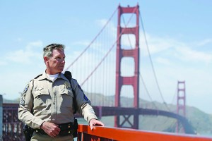In this photo taken Tuesday, April 30, 2013 California Highway Patrol Sergeant Kevin Briggs poses by the Golden Gate Bridge in San Francisco. About 1,500 people have plunged from the bridge, making it one of the world's favorite suicide spots.  During his 20 years patrolling the bridge Briggs has managed to talk many despondent people out of taking the fatal fall. (AP Photo/Eric Risberg)